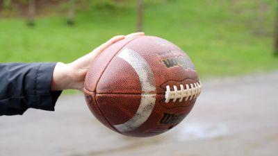 Hand som håller i en amerikansk fotboll.