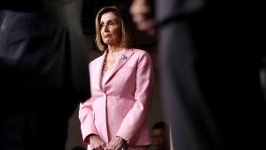 Nancy Pelosi, talman i USA:s representanthusets, iklädd rosa kostym står mellan svartklädda män.