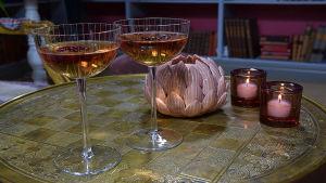 Två drinkglas med tecocktail i på ett bord.