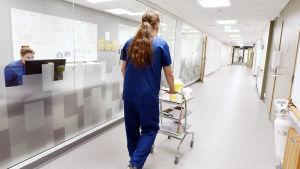 Manlig sjukskötare går i korridor på Mellersta Österbottens Centralsjukhus i Karleby. En kvinnlig anställda sitter bakom en datorskärm i ett intilliggande rum med stora fönster som vetter mot korridoren.