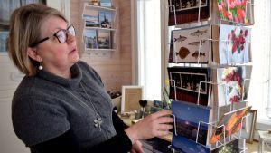 Maria Pick tittar på en ställning med vykort med somriga skärgårdsmotiv.