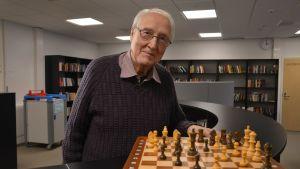 Helge Hedman i Zachariasskolans bibliotek. Han står bredvid ett schackspel.