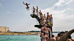Människor som hoppar ner för ett simtorn.