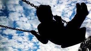 Bild av barn som gungar i en gunga. Barnet syns som en mörk figur mot en ljus bakgrund bestående av blå himmel och vita moln.,
