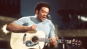 Bill Withers som ung sitter med gitarr i famnen och sjunger.