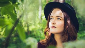 Mona Hirsikangas metsässä kasvien keskellä.