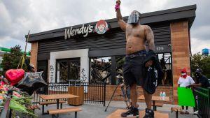 Mies osoittaa mieltään Atlantassa Wendy's ravintolan terassilla.