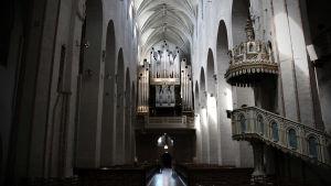 Insidan av Åbo domkyrka med vy över predikstolen och orgeln och kyrkbänkarna.
