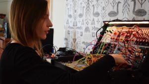 Laura Naukkarinen plockar med sladdar i sin elektroniska musikapparat.