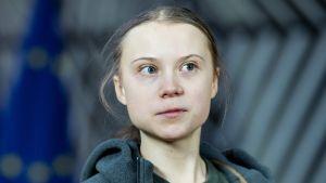 Greta Thunberg tittar åt sidan. I bakgrunden syns en EU-flagga.