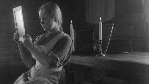 Svartvit bild från början av 1900-talet på en flicka som sitter vid ett bord med två levande ljus och trollbunden tittar in i en spegel som hon håller i med bägge händerna.