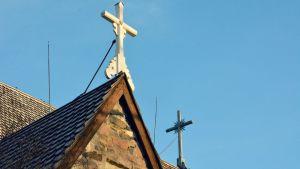Två vita träkors på taket av en kyrka.