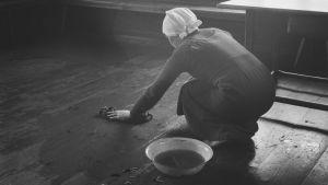Svartvit bild på kvinna som skurar golvet i ett torp på 1930-talet.