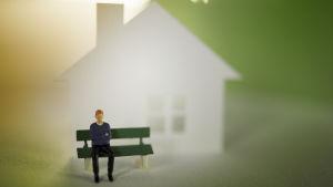 Miniatyyrimies istuu penkillä talon edessä.