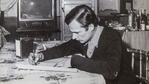 Vilho Hietala skriver vid ett bord.