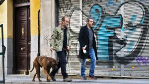 Kaksi miestä ja koira kadulla. Kuva espanjalaisesta elokuvasta Truman.