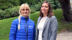 Saija Westerlund-Cook och Janina Andersson står ute i en grön park.