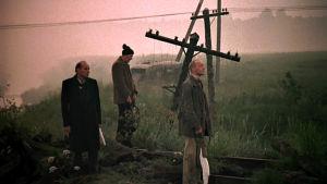 Kolme miestä maisemassa. Kuvakaappaus elokuvasta Stalker.