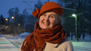 Porträttfoto av dam tagen utomhus vintertid. Damen har på sig en rostbrun hatt och en rostbrun halsduk till en beige kappa. Hon ler.