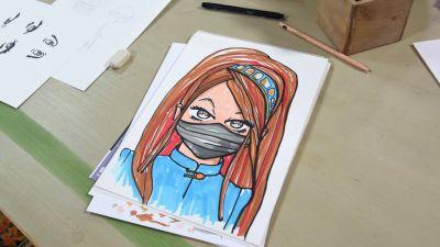 Ett pappersark med ett tecknat kvinnoporträtt. Kvinnofiguren är en ninja tecknad i mangastil. Ninjan har en svart ansiktsmask, långt brunt hår och en blå jacka.