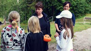 Gunvor Karlsson-Lindholm och Malin Vesalainen talar med några skolbarn som hittat en lunchlåda i skogen.