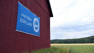 """En ladugårdsvägg där det hänger ett skynke med texte """"Mat från eget land"""" och en svan på bilden."""