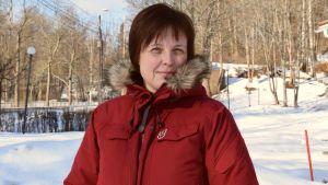 Karin Erlandsson i en röd rock i ett vintrigt landskap.
