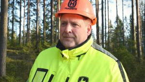 Kristian Blomqvist står i skogen iklädd skyddshjälm och reflexväst.