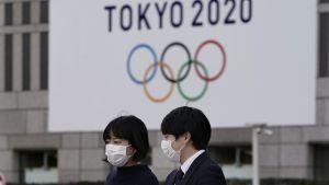 två personer står med ansiktsmasker framför en OS-skylt.