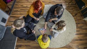 Perhe pelaa kimbleä lattialla.