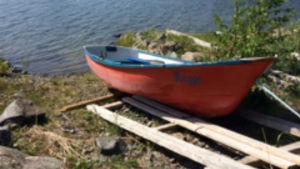 En orange roddbåt uppdragen på en strand.