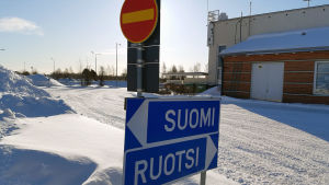 """Trafikskyltar med texten """"Sverige"""" och """"Finland"""" vid snöig gräns i Torneå"""