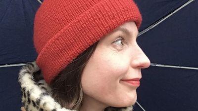 Laura Naukkarinen lähikuvassa sateenvarjon alla