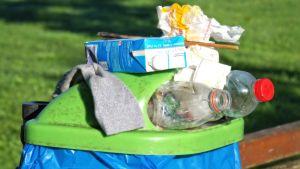 Jo täynnä olevan roskiksen päällä on roskia.