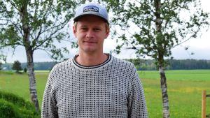 Filip Forss framför en grön åker.