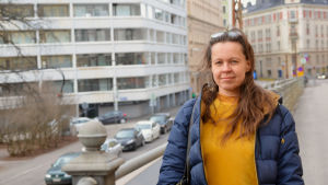 Pauliina Seppälä står på en väg vid ett räcke. Hon ser in i kameran, och det är mulet. Hon har på sig en blå jacka, och under det en gul ylletröja.
