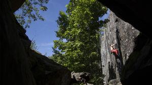 En man klättrar upp för ett stup. Bilden är tagen på avstånd.
