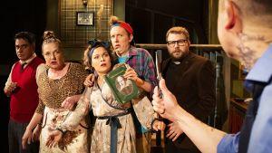 6 skådespelare med olika roliga uttryck i kropp och ansikte  och brokiga kläder på studioscenen på ÅST. En man i förgrunden med ryggen mot publiken har en kniv i handen som han höjer mot de andra