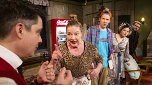 skådepelare mot svart bakgrund. Två kvinnor och tre män. Coca Cola- automat och möbler.