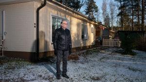 Mies seisoo talon edessä, huurteinen piha