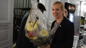 Sandra Bergqvist ser glad ut med en bukett blommor i handen.