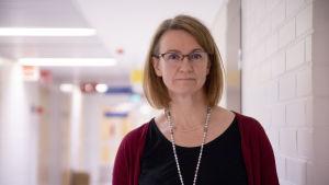 Katariina Kauniskangas, en dam med ljust hår och glasögon, står i en sjukhuskorridor.