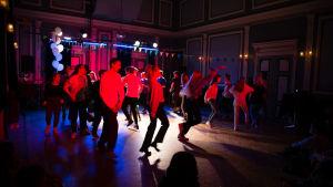 En grupp tonåringar dansar i en sal upplyst med röd belysning.