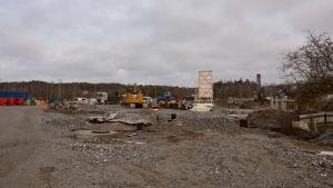 En stor knölig grusplan med olika byggmaskiner i  bakgrunden.