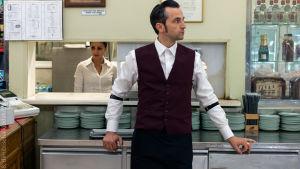 Mies seisoo ravintolatiskin edessä ja katsoo oikealle.