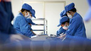 Lääketehtaan suoja-asuisia työntekijöitä.
