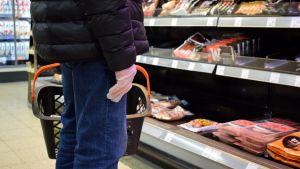 En äldre person står vid köttdisken i matbutiken med plasthandske på handen.