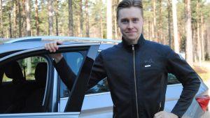 Emil Lindholm står vid en öppnad bildörr.