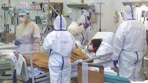 Suojapukuiset ihmiset hoitavat potilasta.