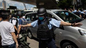 Poliisi estää väkijoukkoa lähestymästä autoa.